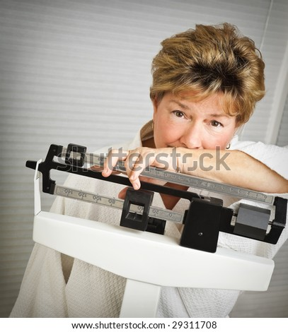 Closeup of a pretty but worried mature woman weighing herself on a medical scale. - stock photo