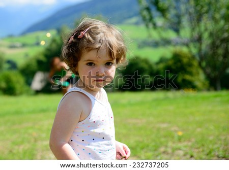 closeup of a pretty little girl in the garden and she look the camera