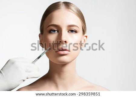 Closeup of a pretty woman does injection to nasolabial fold  - stock photo