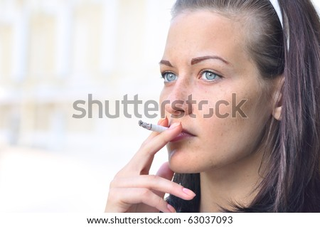 closeup of a pretty woman smoking at the street - stock photo
