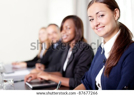 Closeup of a pretty young businesswoman- smiling at the camera - stock photo