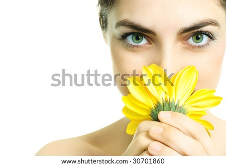 closeup of a pretty young woman smelling a yellow flower - stock photo