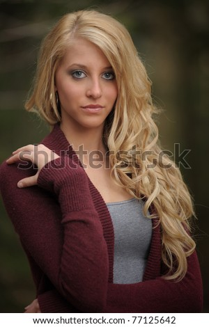 Closeup of a pretty young woman standing with blonde hair and blue eyes - stock photo