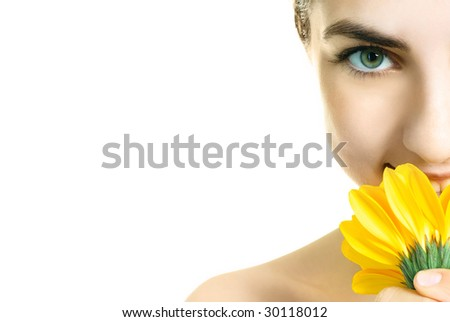 closeup of a pretty young woman with a yellow flower - stock photo