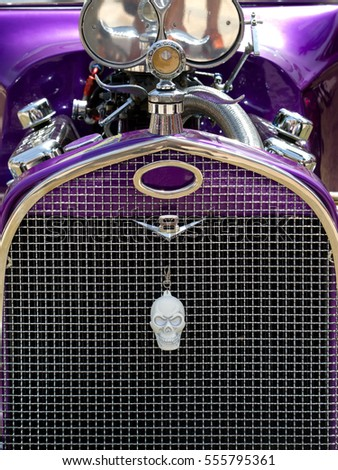 closeup of a purple v8 hot rod with a skull on the chrome grill at a