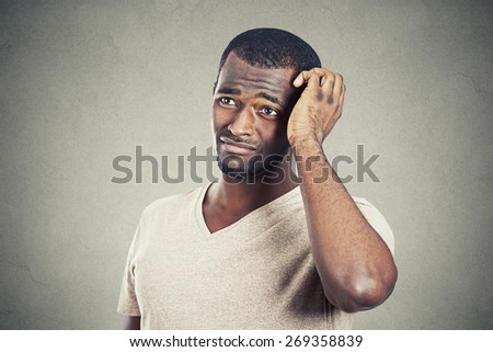 Closeup of a puzzled young man  - stock photo