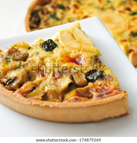 closeup of a quiche with goat cheese and vegetables - stock photo