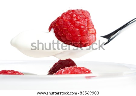 closeup of a raspberry on a spoon with yogurt over a dessert with raspberries on white background - stock photo