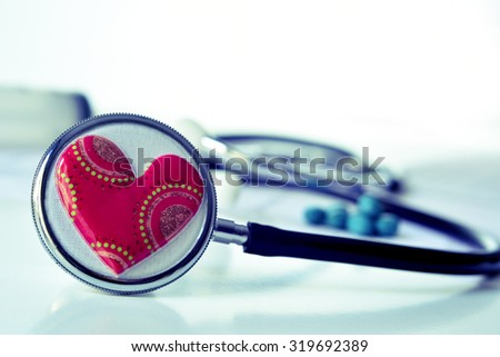 closeup of a red heart on a stethoscope for the cardiovascular health - stock photo