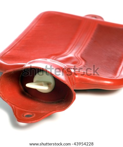 Closeup of a red hot water bottle with the plug in focus - stock photo