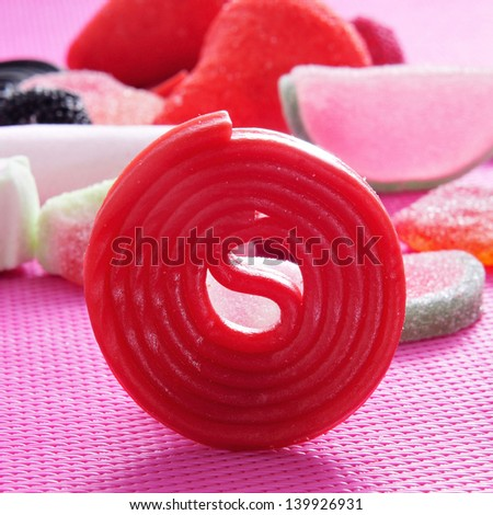 closeup of a red liquorice wheel and a pile of different candies - stock photo