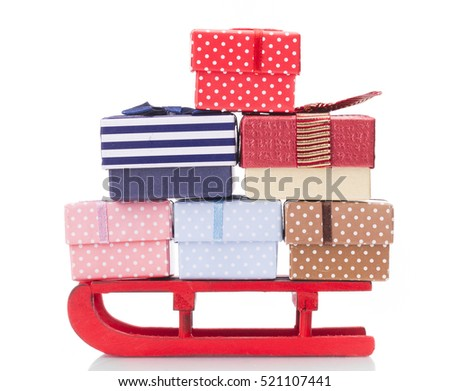 Closeup of a red sled full of gift boxes, isolated on white background