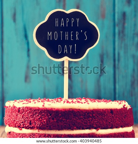 closeup of a red velvet cake topped with a chalkboard in the shape of a thought bubble with the text happy mothers day, against a blue rustic wooden background - stock photo