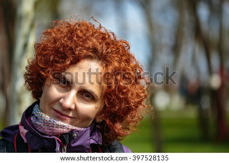 Closeup of a redhead curly hair woman outdoor - stock photo