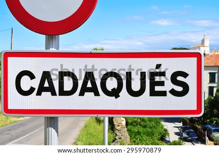closeup of a road sign with the name Cadaques written in it at the entrance of Cadaques, in the Costa Brava, Spain - stock photo