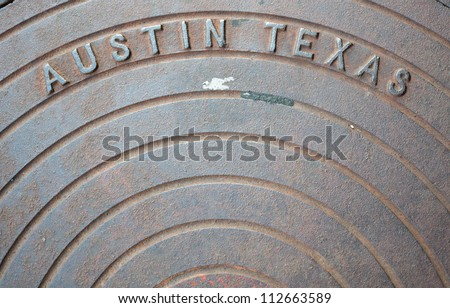 "Closeup of a rusted manhole cover with the words ""Austin Texas"" - stock photo"