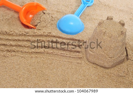 closeup of a sandcastle and beach shovels on the sand - stock photo