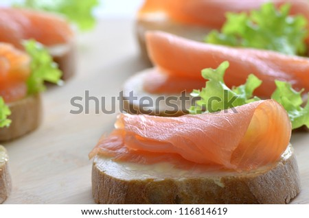 Closeup of a sandwich with smoked salmon, butter and lettuce leaf. Shallow dof.