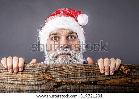 Closeup of a  scared man with frozen beard and mustache wearing red santa claus  over gray background