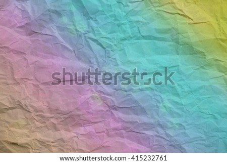 Closeup of a section of crumpled wrapping paper overlaid with colors