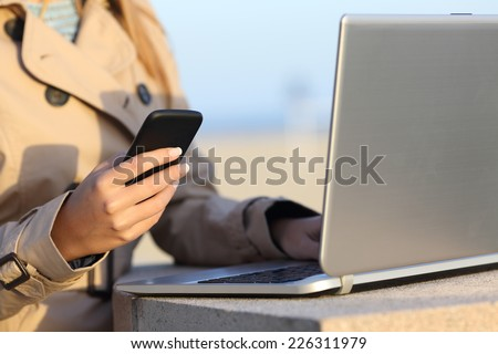 Closeup of a self employed woman hand working with a laptop and phone outdoor on the beach - stock photo