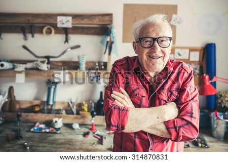 Closeup of a senior craftsman in his workshop - stock photo
