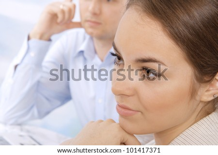 Closeup of a serious young business executive in a meeting with colleagues - stock photo
