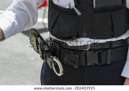 Closeup of a set of handcuffs in a leather holster on a British policeman's belt - stock photo