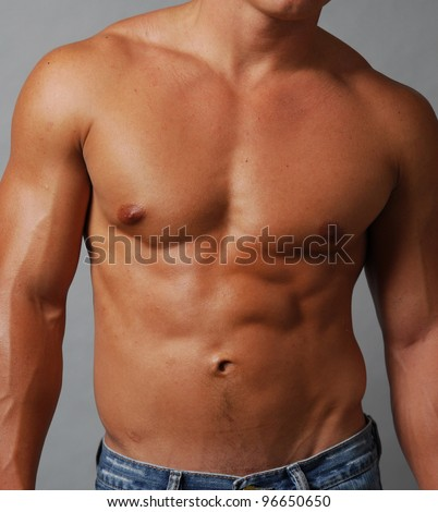 closeup of a shirtless muscular male torso, chest and abdomen - stock photo