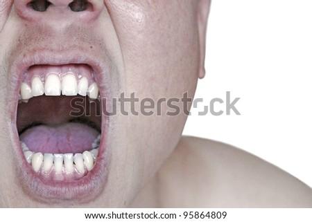 Closeup of a shouting man's mouth baring his teeth. - stock photo