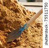 Closeup of a shovel digging into pile of building sand - stock photo