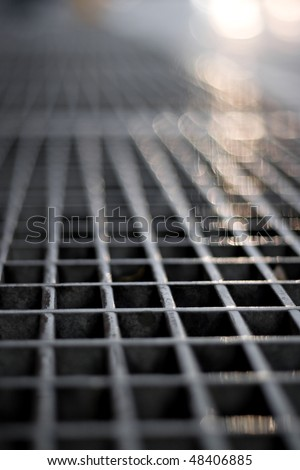 Closeup of a sidewalk subway grate with shallow depth of field. - stock photo