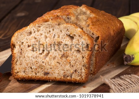 Closeup of a slice of banana nut sweet bread on a wooden cutting board