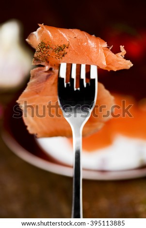 closeup of a slice of marinated smoked salmon seasoned with dill in a fork - stock photo
