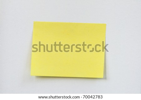 closeup of a small blank yellow sticky note stuck on a white wall