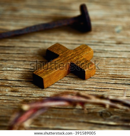 closeup of a small wooden cross, a depiction of the crown of thorns of Jesus Christ and a nail on a wooden surface - stock photo