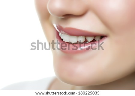 Closeup of a smiling face of a woman with lips, nose and teeth