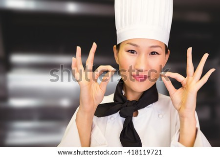 Closeup of a smiling female cook gesturing okay sign against deep fat fryers - stock photo