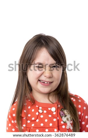 Closeup of a smiling little girl blinking over white background - stock photo