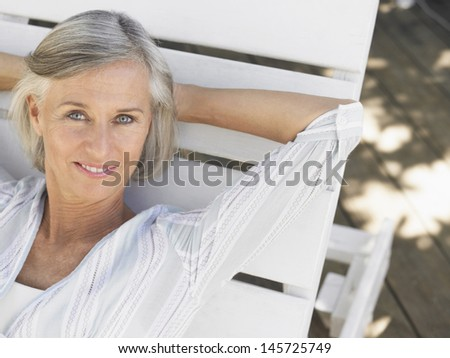 Closeup of a smiling middle aged woman reclining on sunlounger - stock photo