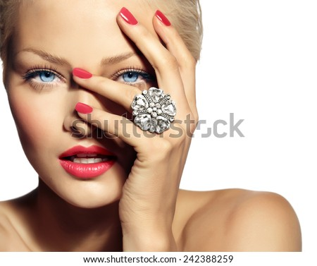 Closeup of a smiling model wearing a large ring. Most focus is on hand.