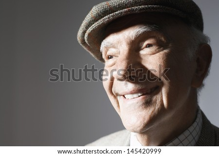 Closeup of a smiling senior businessman in flat cap against gray background - stock photo
