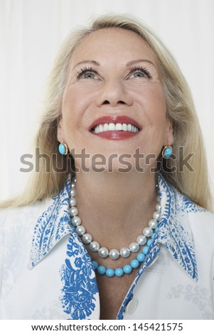 Closeup of a smiling senior woman looking up against white background - stock photo