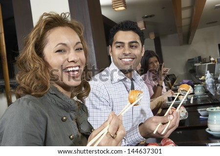 Closeup of a smiling woman and friends eating sushi with chopsticks in a restaurant - stock photo