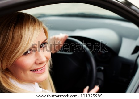 Closeup of a smiling woman driver seated at the wheel of a car looking back out of the window at the camera