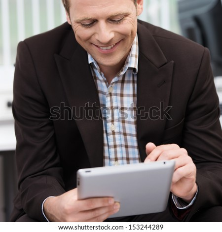 Closeup of a smiling young business man sitting using a tablet-pc scrolling with his finger on the touchscreen - stock photo
