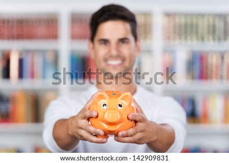 Closeup of a smiling young man showing a piggy bank in the library. - stock photo