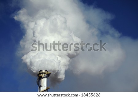 Closeup of a smoke stack, quivering with heat, spewing steam and pollutants against a clear blue sky - stock photo