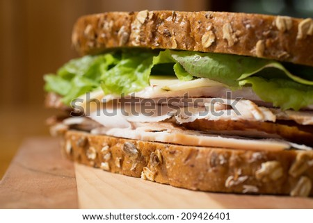 Closeup of a smoked turkey and cheese sandwich.