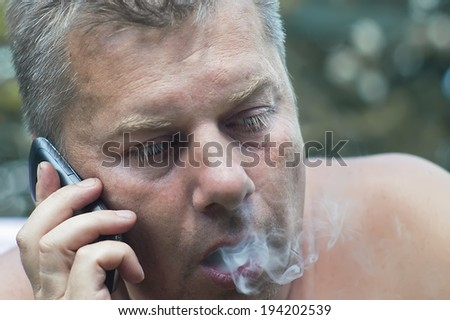 Closeup of a smoking man talking on a mobile phone. Outdoor shot. Concept of the always busy people - stock photo